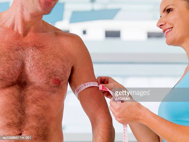 woman measuring man's biceps, close-up - female hairy chest stock pictures, royalty-free photos & images
