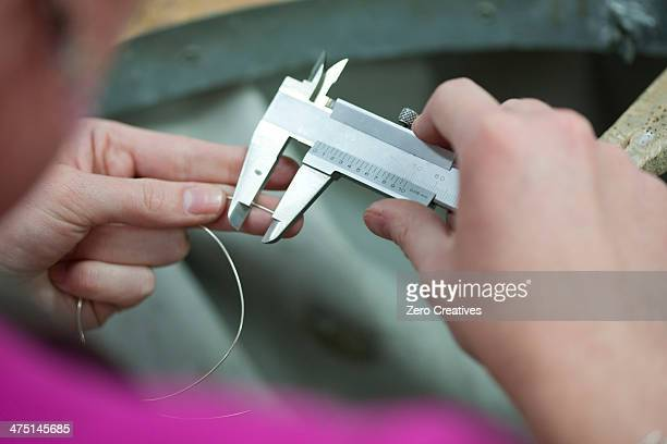 Woman measuring metal wire for jewelry