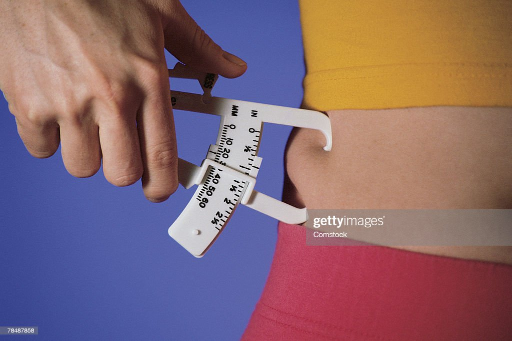 Woman measuring percentage of body fat on waist : Stock Photo