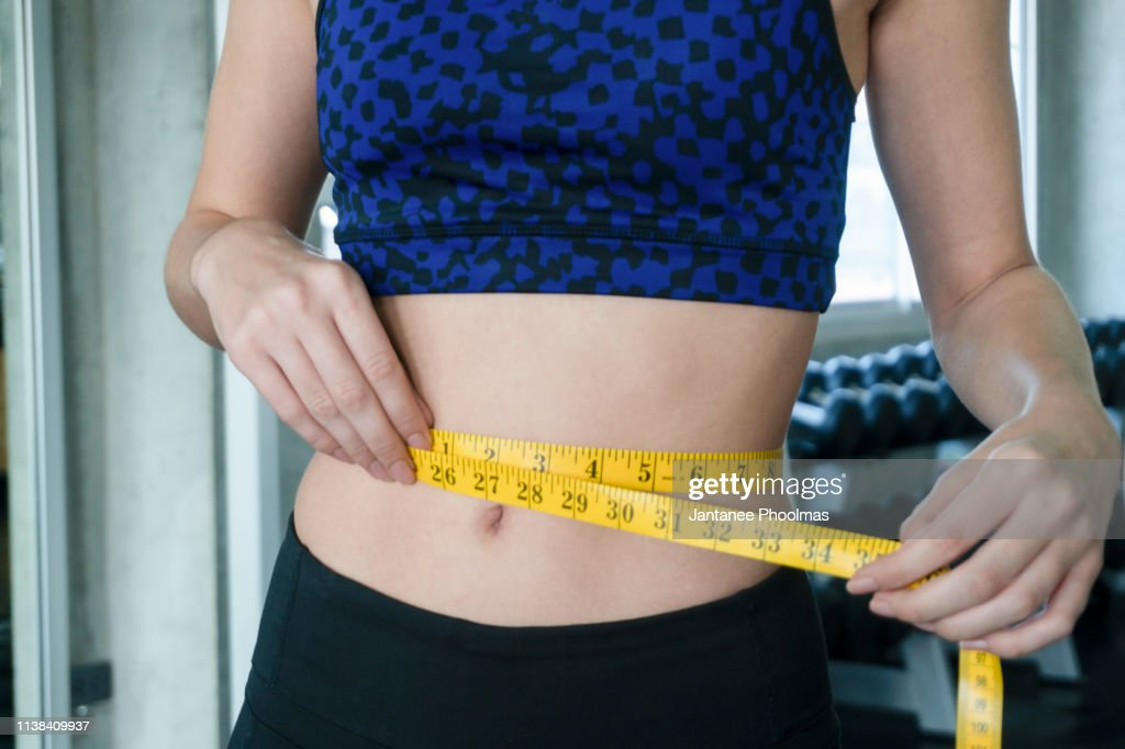 Woman measuring perfect shape of beautiful waist, healthy lifestyles concept : Stock Photo
