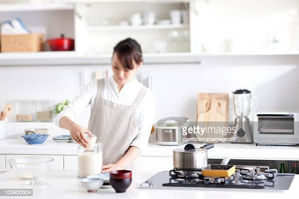 Woman Measuring Rice With a Measuring Cup