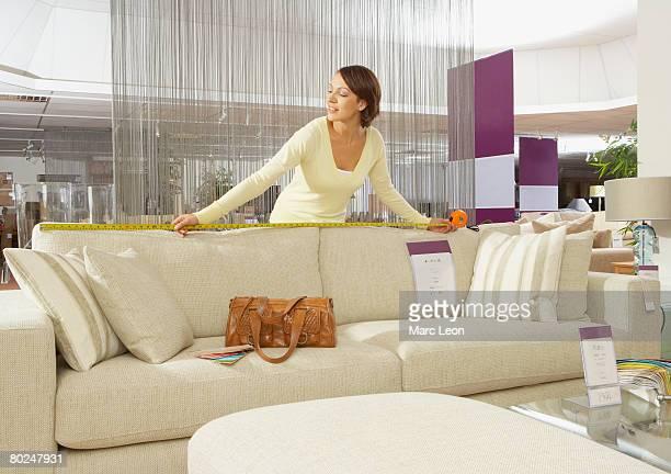 Woman measuring sofa in furniture store.