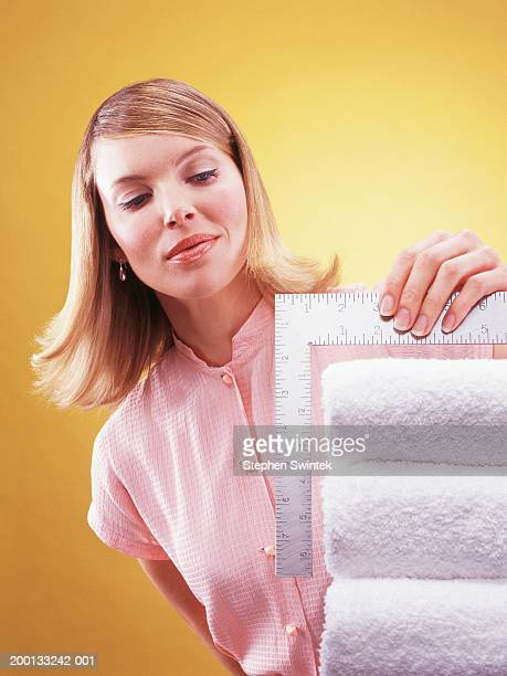 Woman measuring stack of folded towels