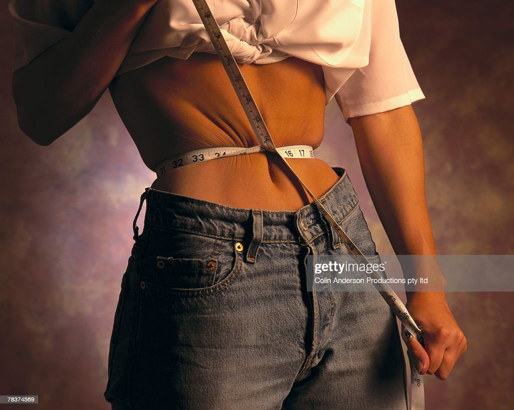 Woman measuring waist : Stock Photo