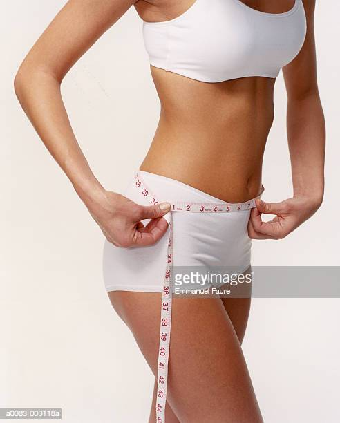 woman measuring waist - measuring stock photos and pictures