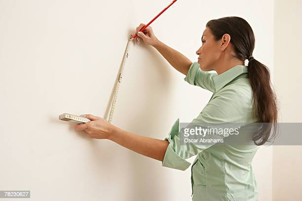 woman measuring wall with folding rule