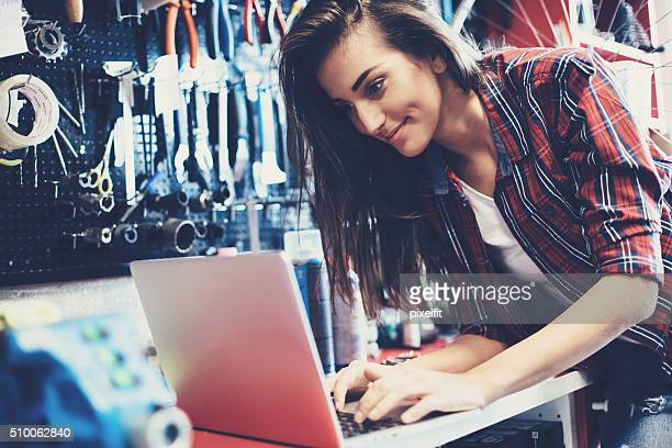 Woman mechanic working on a laptop