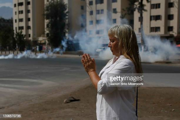 A woman meditates during protests against the government of Sebastián Piñera on its second anniversary on March 11 2020 in Santiago Chile Massive...