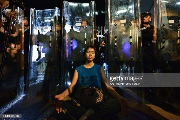 A woman meditates in front of a line of riot police standing guard with their shields outside the government headquarters in Hong Kong early on June...