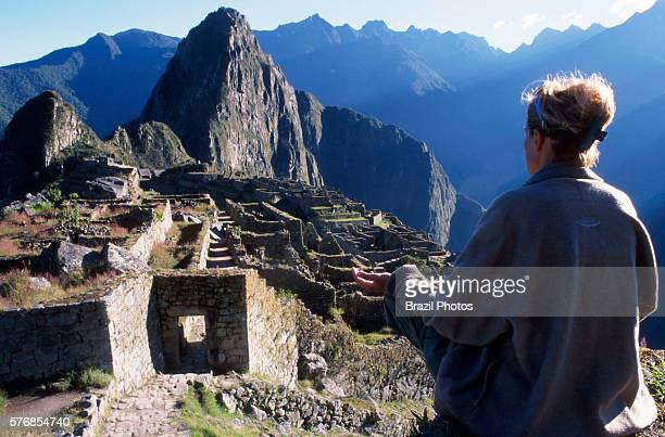 Woman meditates in Machu Picchu a 15thcentury Inca citadel situated on a mountain ridge 2430 metres above sea level in the Cusco Region the most...