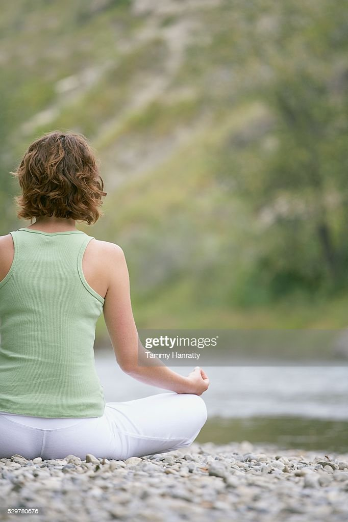 Woman meditating at edge of river : Stock Photo