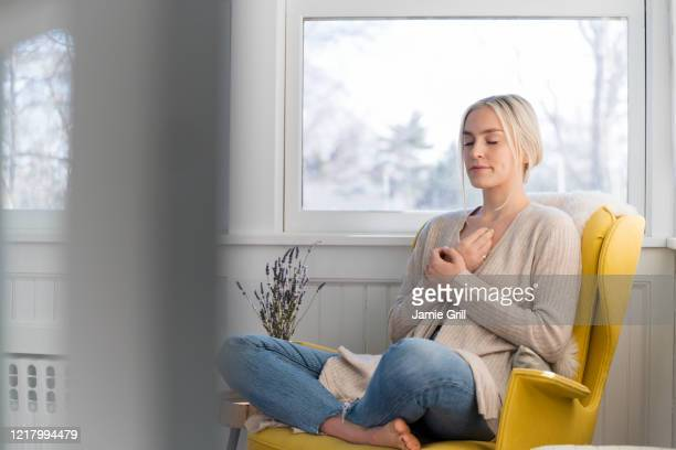 woman meditating at home - zen like stock pictures, royalty-free photos & images