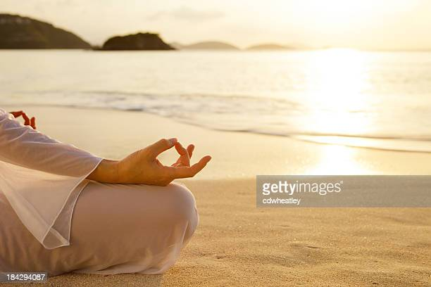 woman meditating at sunset on the Caribbean beach
