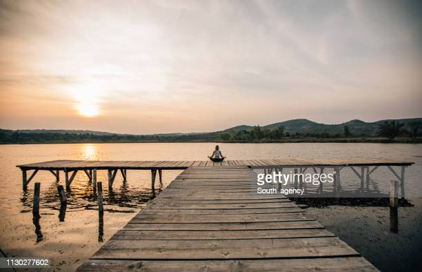 woman meditating by a beautiful lake - zen like stock pictures, royalty-free photos & images