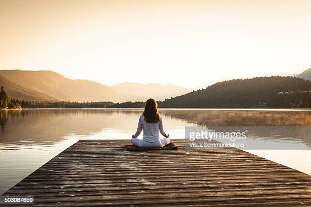 Woman meditating by lake.