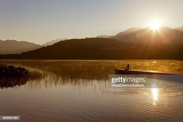 Frau Meditieren am See.