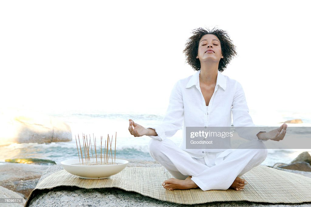 Woman meditating by ocean : Stock Photo