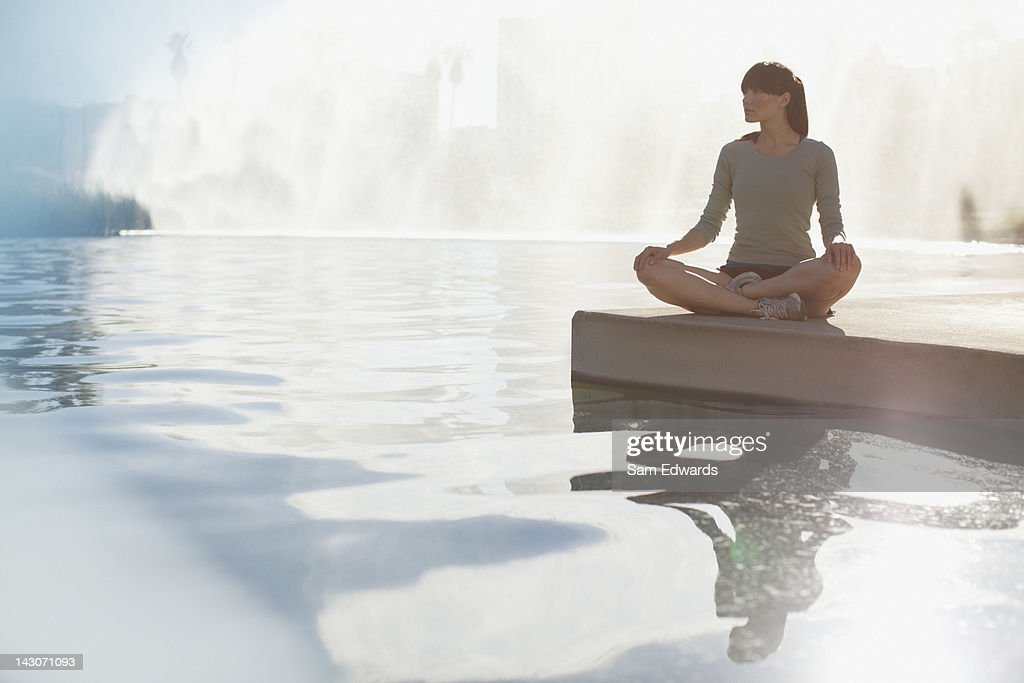 Woman meditating by still pool : Stock Photo
