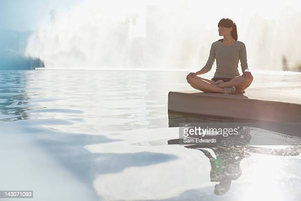Woman meditating by still pool