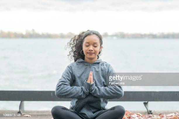 Woman meditating by the water