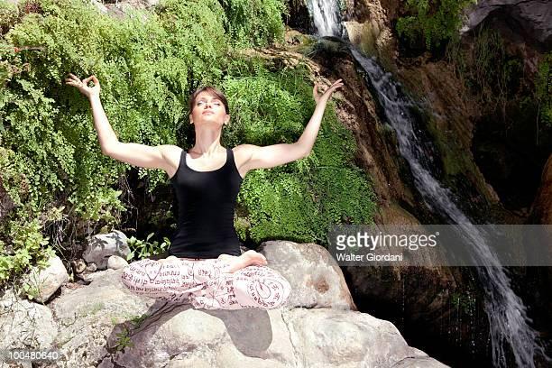 Woman meditating by waterfall