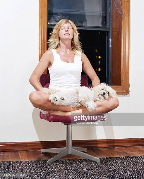 Woman meditating, dog resting on lap