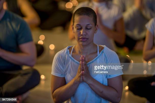 Woman Meditating In A Dim Room