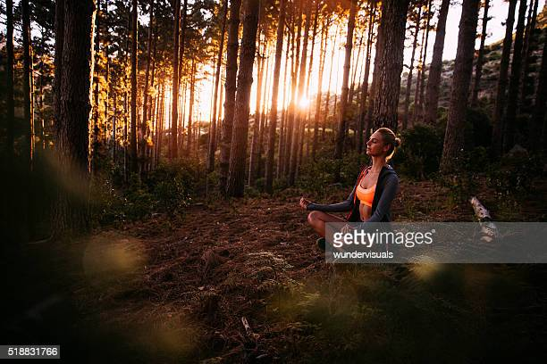 Woman meditating in a yoga pose in a morning forest