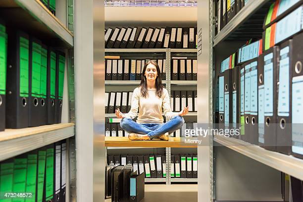 Woman meditating in company finance file archive