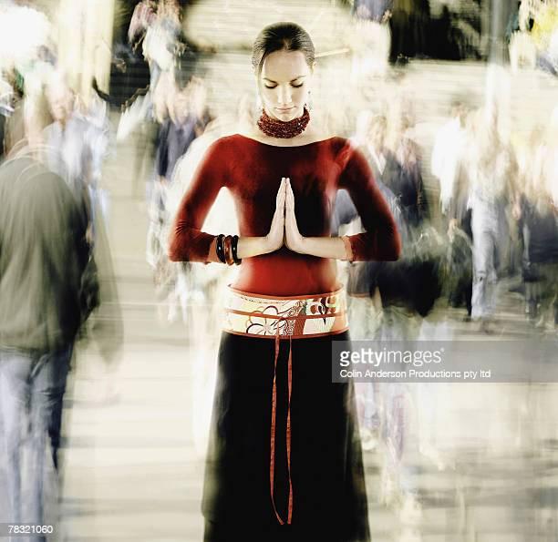 Woman meditating in crowd