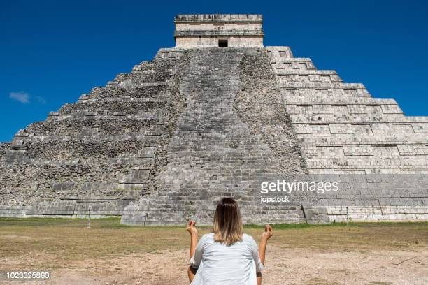 woman meditating in front of mayan pyramid of chichen itza in mexico - mayan people stock photos and pictures