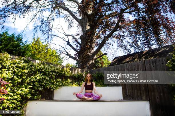 A woman meditating in her garden full of flowers and plants, in front of a big tree in a beautiful day in London