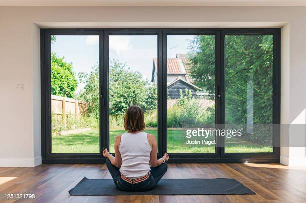 woman meditating in living room - sliding door stock pictures, royalty-free photos & images