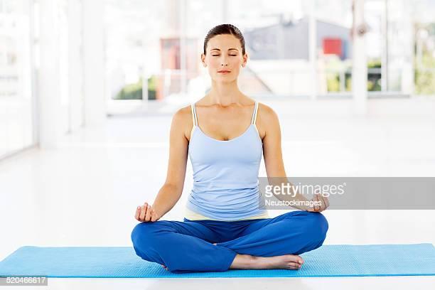 Femme méditer en Position du Lotus au cours de Yoga