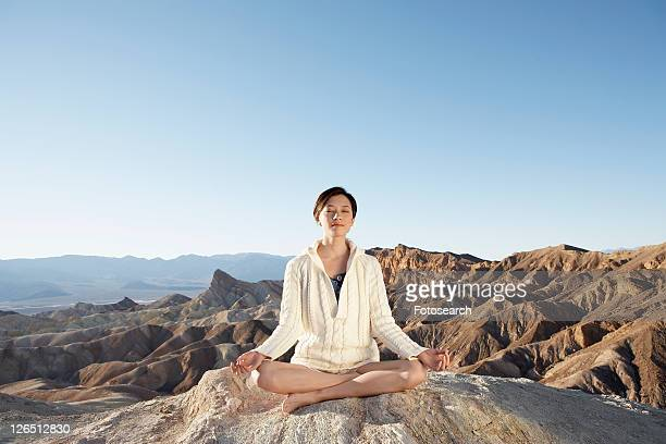 woman meditating in lotus position in desert, death valley, california, usa - front view ストックフォトと画像