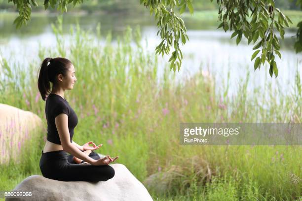 Woman meditating in lotus position in the park