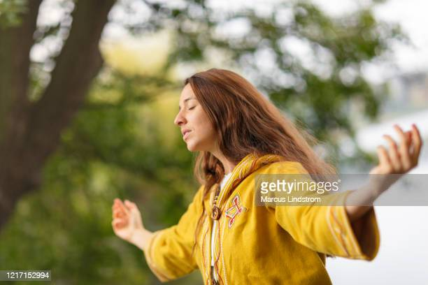 a woman meditating in nature - chanting stock pictures, royalty-free photos & images