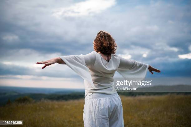 woman meditating in nature - good posture stock pictures, royalty-free photos & images