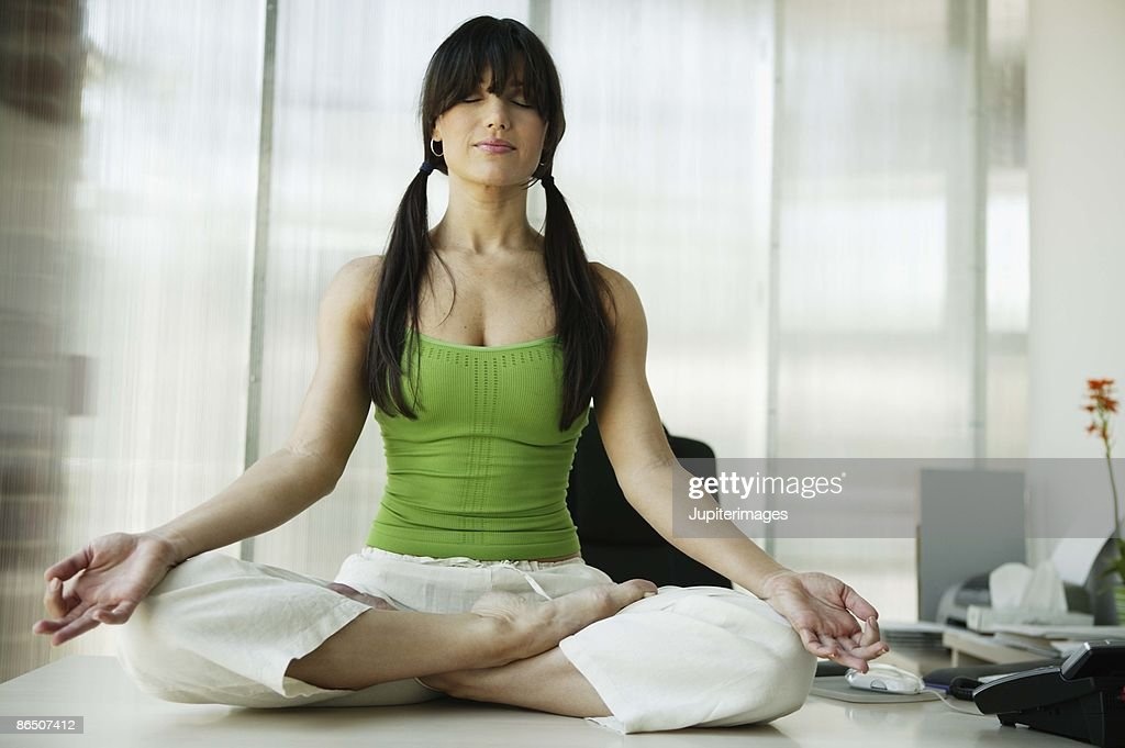 Woman meditating in office : Stock Photo