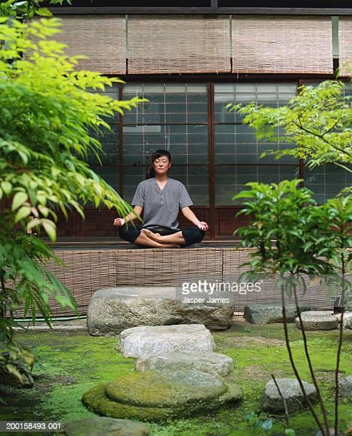 woman meditating in temple garden - 胡坐 ストックフォトと画像