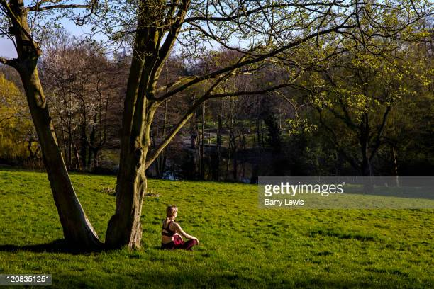 Woman meditating in the afternoon sun in Waterlow park during the Coronavirus pandemic on 27th March 2020 in London, United Kingdom. Social...