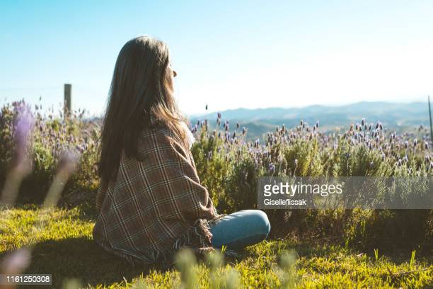 woman meditating in the nature, in a flower field, with closed eyes - spirituality stock pictures, royalty-free photos & images