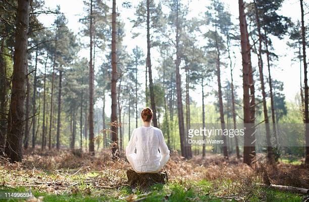 Woman meditating in woodland setting.