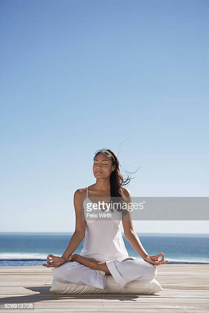Woman meditating near ocean