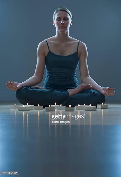 woman meditating next to candles - cero foto e immagini stock