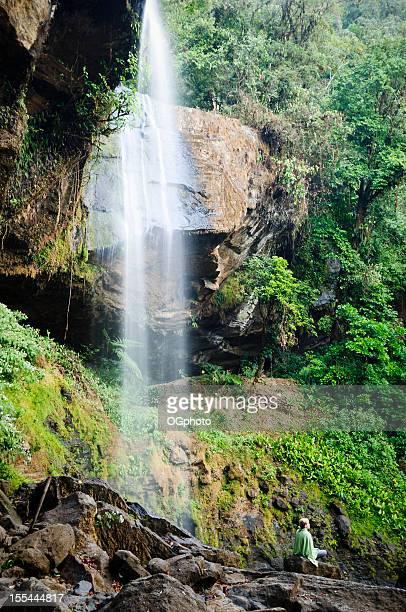 Woman meditating next to waterfall