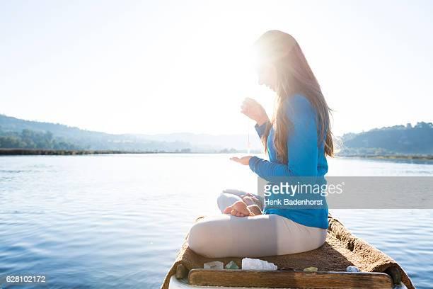 Woman Meditating On A Calm Lake