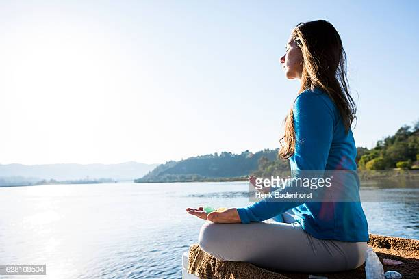 woman meditating on a calm lake - crystal stock pictures, royalty-free photos & images