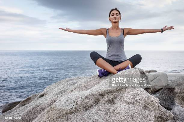 woman meditating on boulder - yoga stockfoto's en -beelden