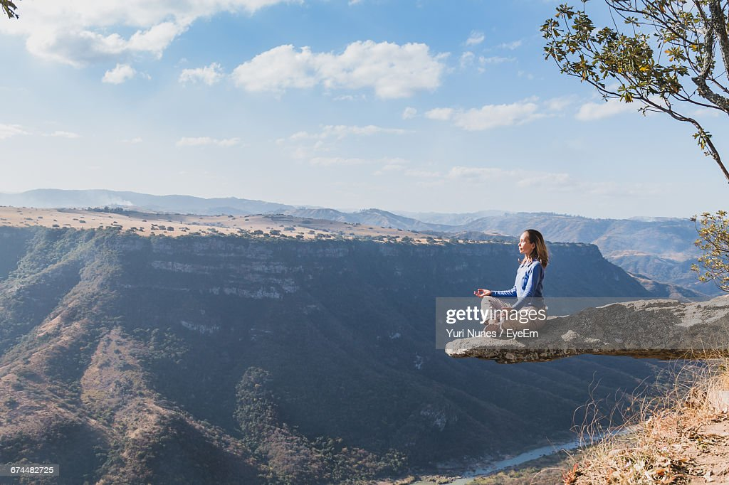 Woman Meditating On Cliff By Mountains Against Sky : Stock Photo